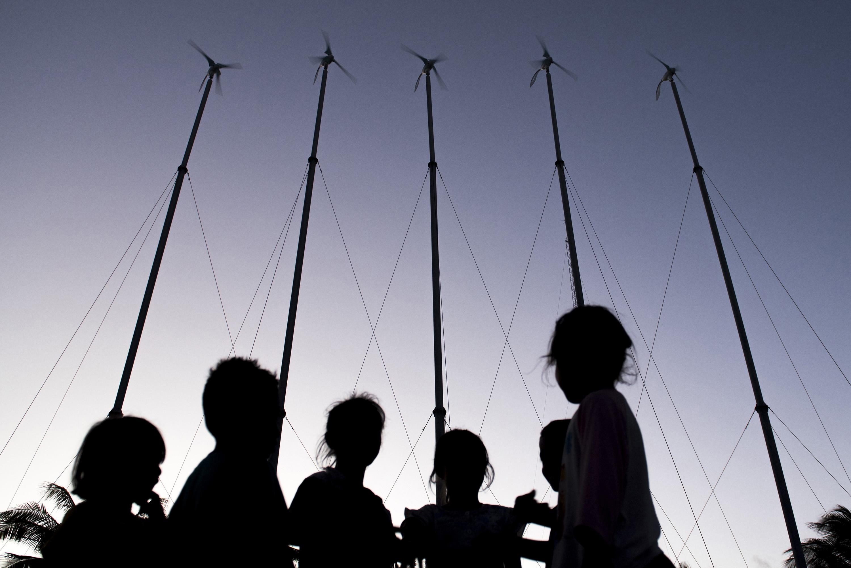 Siluet anak-anak saat bermain berlatarbelakang pembangkit listrik tenaga angin di Desa Bo'a, Rote Ndao, Nusa Tenggara Timur. Sebanyak 120 rumah di desa tersebut menggunakan listrik dari lima unit kincir angin dan 78 unit panel panas matahari. ANTARA FOTO/M Agung Rajasa.