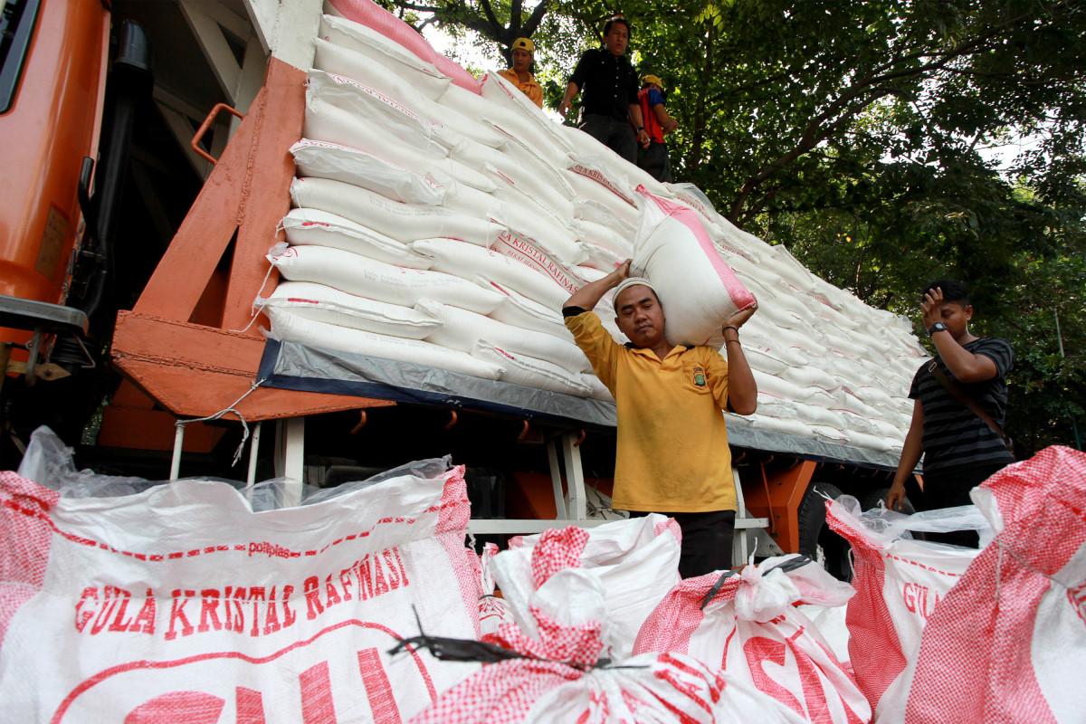 Petugas menurunkan barang bukti gula pasir rafinasi atau gula pasir pabrikan di Polda Metro Jaya, Jakarta, Rabu (24/6). Polda Metro Jaya menggagalkan upaya penggelapan dan atau pertolongan jahat gula pasir rafinasi untuk dijual ke pasar yang dilakukan oleh tiga tersangka yaitu M.S, SP dan U dengan cara mengurangi satu kg dari setiap karung dengan total yang diambil sebanyak 700kg. ANTARA FOTO/Muhammad Adimaja/Asf/kye/15.
