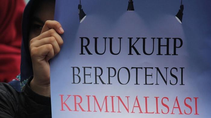 Massa yang tergabung dalam Jaringan Kerja Penanganan Kasus Kekerasan terhadap Perempuan dan Anak membentangkan poster saat menggelar aksi damai menolak RUU KUHP di Surabaya, Kamis (15/2/2018). ANTARA FOTO/Moch Asim