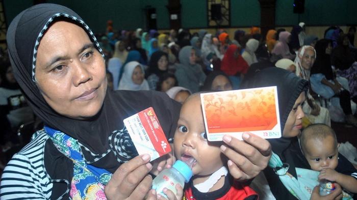 Warga menunjukkan Kartu Keluarga Sejahtera saat Penyaluran Bantuan Sosial Program Keluarga Harapan (PKH) dan Bantuan Sosial Pangan Beras Sejahtera di Gedung Tegar Beriman, Cibinong, Kabupaten Bogor, Jawa Barat, Jum'at (13/4/2018). ANTARA FOTO/Arif Firmansyah
