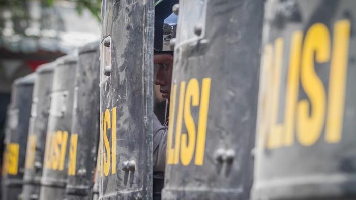 Petugas Kepolisian berlindung saat melakukan pengamanan eksekusi lahan permukiman warga di Kentingan Baru, Solo, Jawa Tengah, Rabu (19/12/2018).  ANTARA FOTO/Mohammad Ayudha/foc.