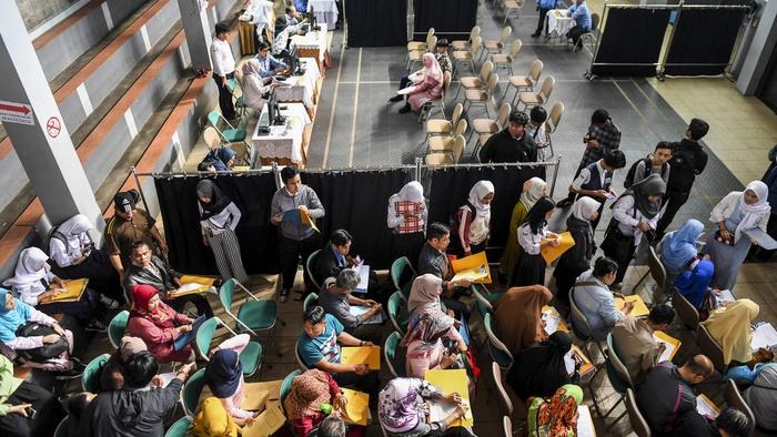 Orangtua dan calon siswa mengantre penyerahan dan pemeriksaan berkas pendaftaran Penerimaan Peserta Didik Baru (PPDB) 2019 tingkat SMA-SMK di SMAN 2 Bandung, Jawa Barat, Senin (17/6/2019).ANTARA FOTO/M Agung Rajasa.