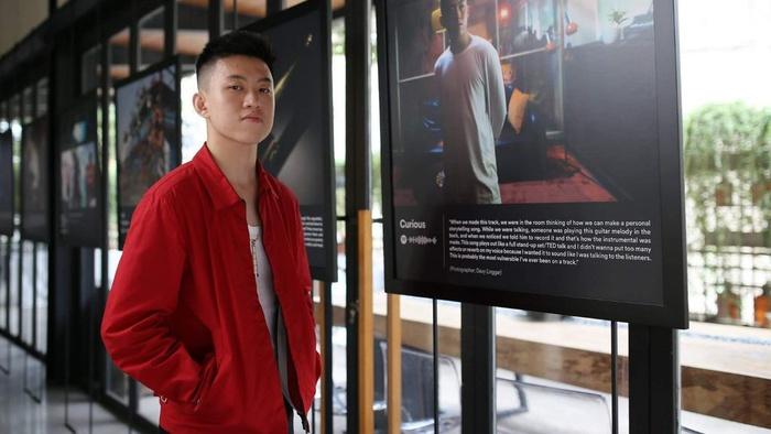 Rich Brian berpose di depan karya yang dipamerkan dalam The Sailor Experience, pameran interaktif hasil kerjasamanya dengan Spotify. FOTO/maverick.co.id