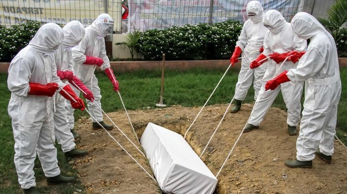 Sejumlah petugas medis memasukkan peti jenazah pasien positif COVID-19 saat simulasi pemakaman di Lhokseumawe, Aceh, Jumat (17/4/2020). ANTARA FOTO/Rahmad/pras.