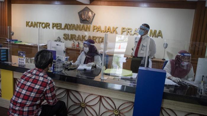 Petugas pajak dengan memakai pelindung wajah dan dibatasi sekat kaca melayani warga wajib pajak dengan layanan langsung atau tatap muka di Kantor Pelayanan Pajak (KPP) Pratama, Solo, Jawa Tengah, Senin (15/6/2020).  ANTARA FOTO/Mohammad Ayudha/wsj.