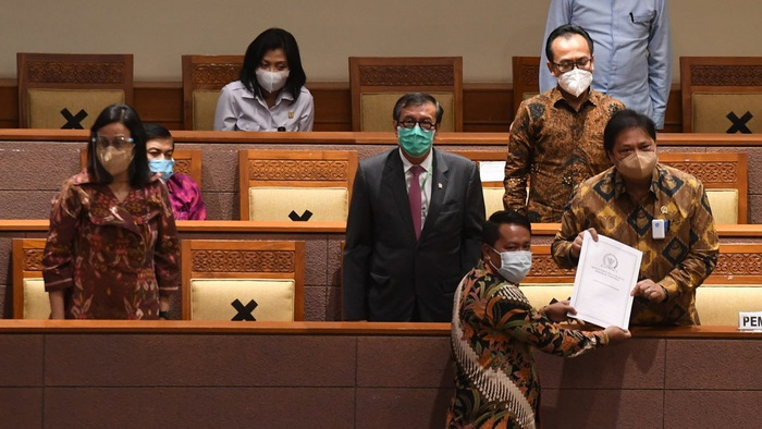 Menko Perekonomian Airlangga Hartarto (kanan) didampingi Menkumham Yasonna Laoly (kedua kiri) dan Menteri Keuangan Sri Mulyani (kiri) menerima laporan akhir dari Ketua Badan Legislasi DPR  Supratman Andi (bawah) saat pembahasan tingkat II RUU Cipta Kerja pada Rapat Paripurna DPR di Kompleks Parlemen, Jakarta, Senin (5/10/2020). ANTARA FOTO/Hafidz Mubarak A.